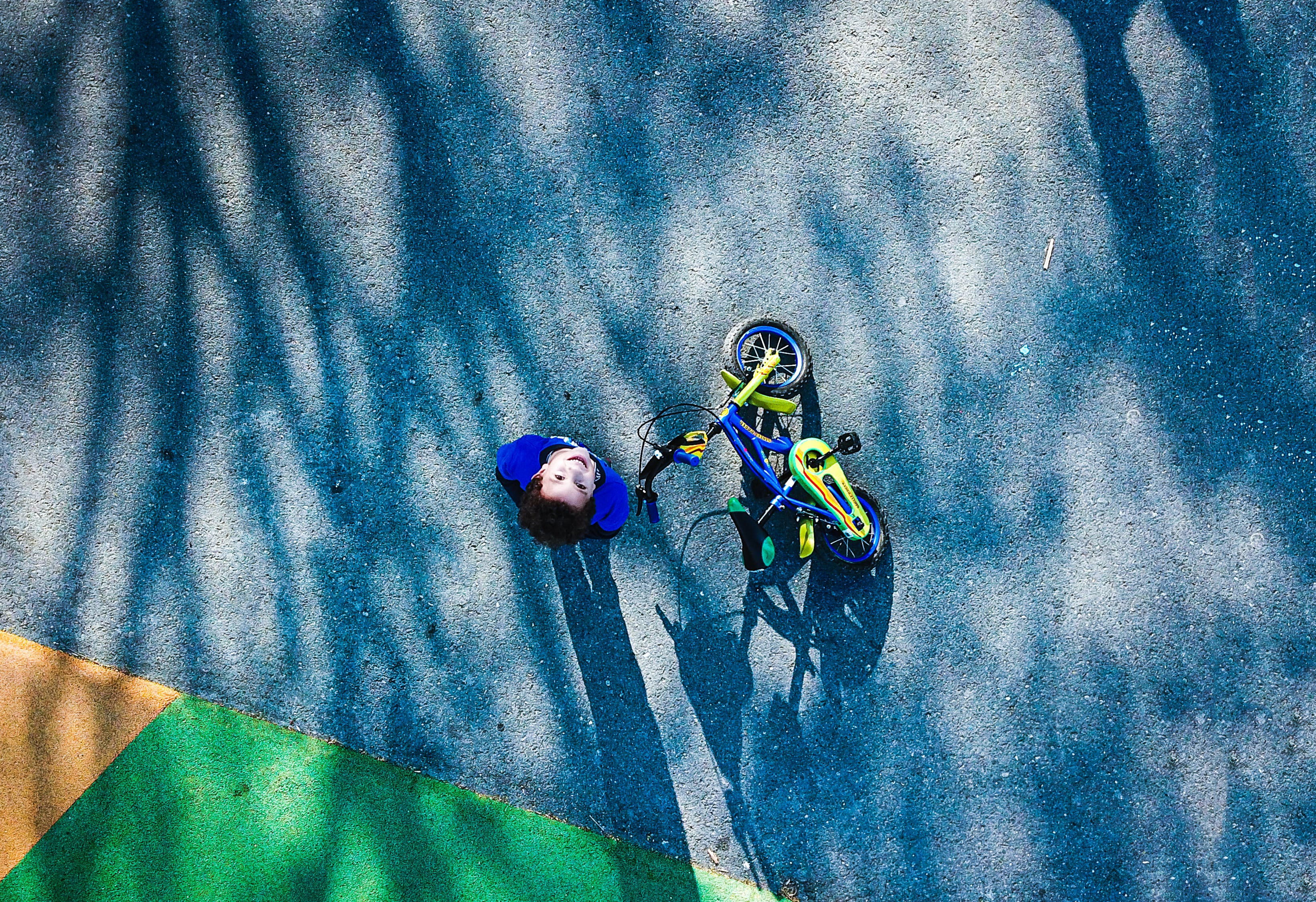 Top View Photo of Kid Near Bicycle