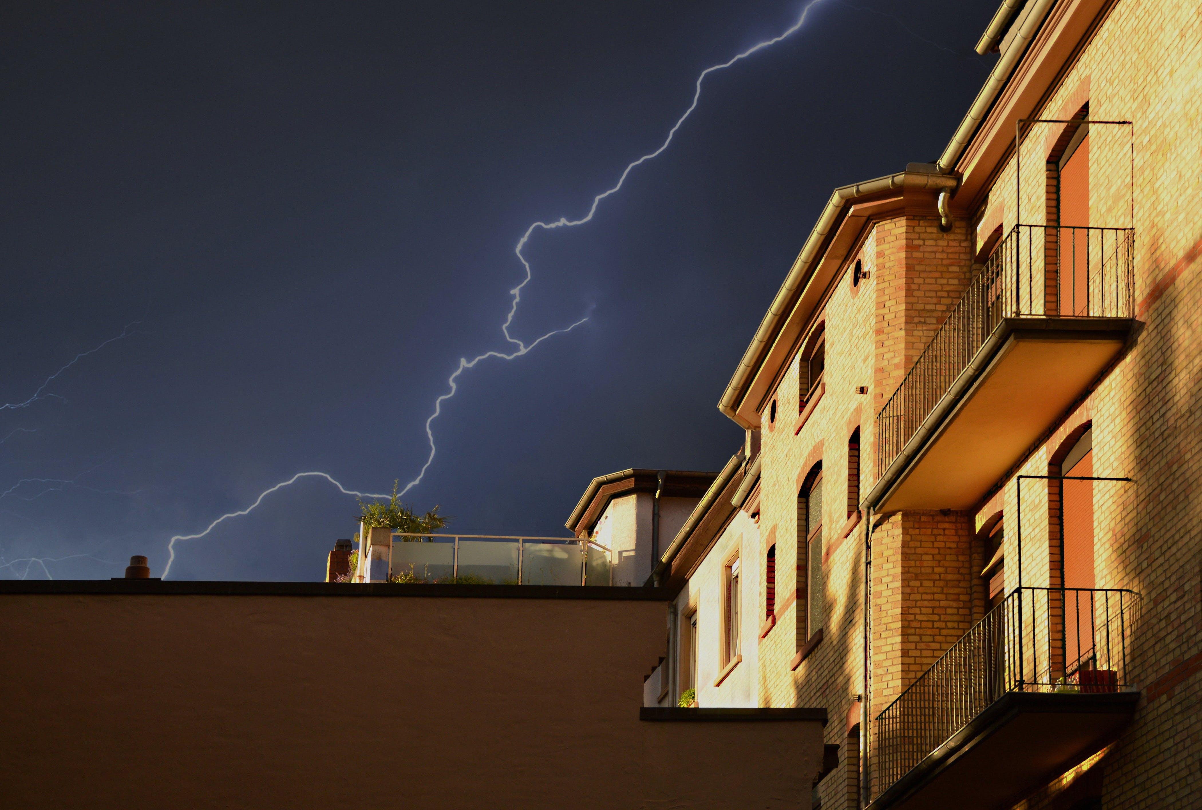 Yellow Building Under Thunderstorm in Black Sky