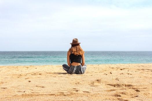 Woman Sitting on Seashore at Daytime