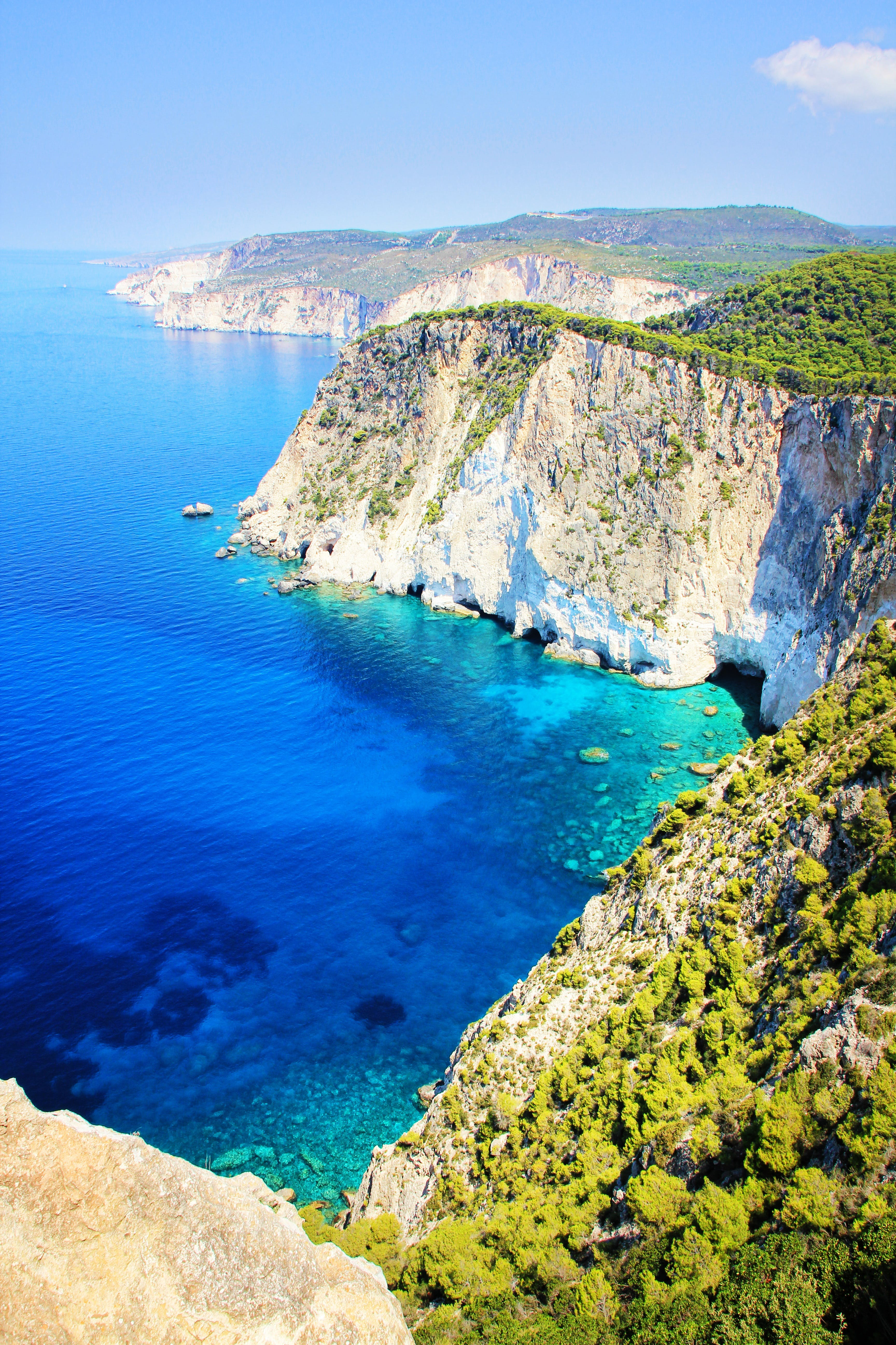 Blue Deep Body of Water Near Cliff With Green Trees Under Blue Sky