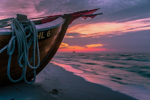 Brown Wooden Boat on Shore during Sunset