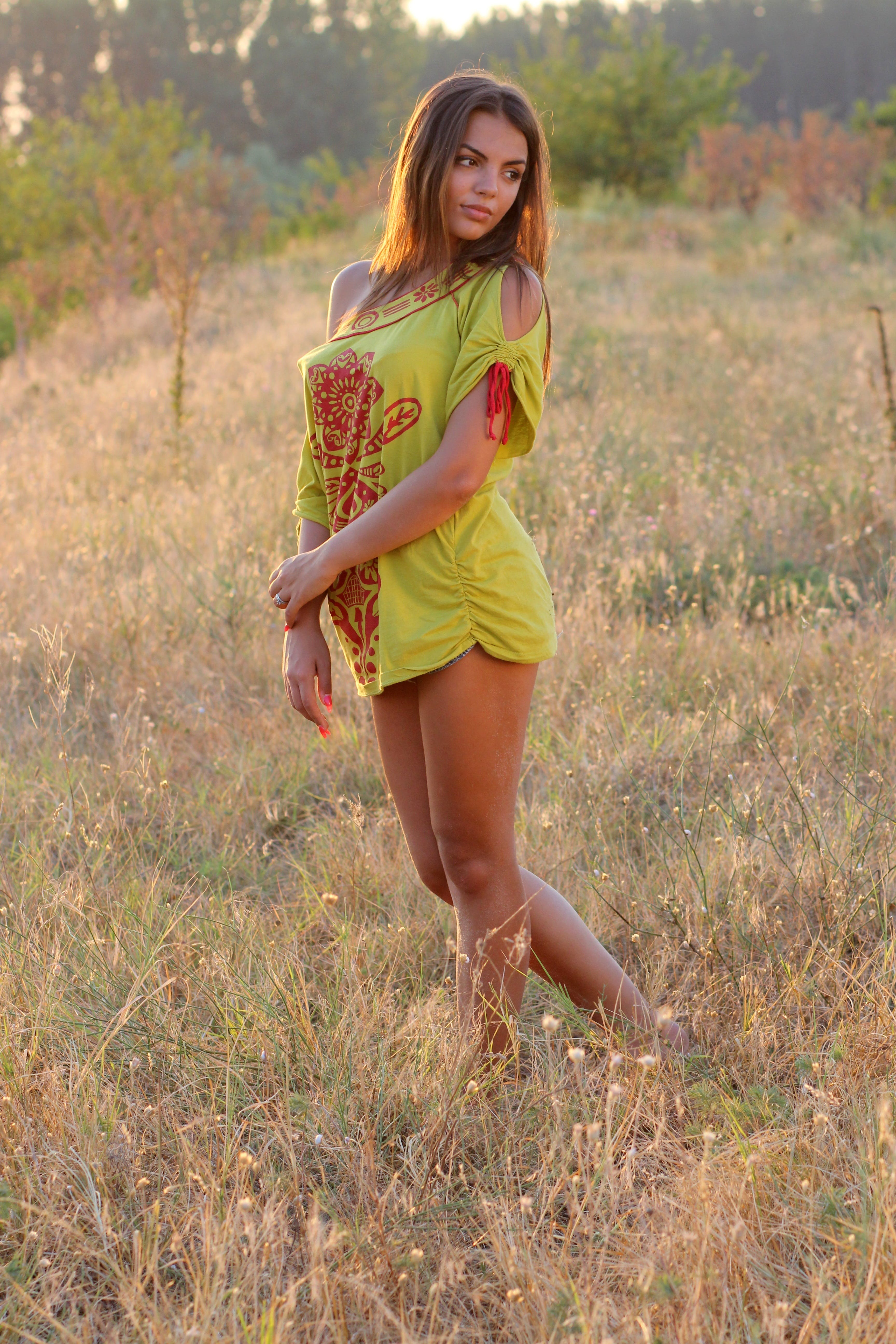 Woman in Yellow Red Floral One Shoulder Shirt Standing on Brown Grass during Daytime