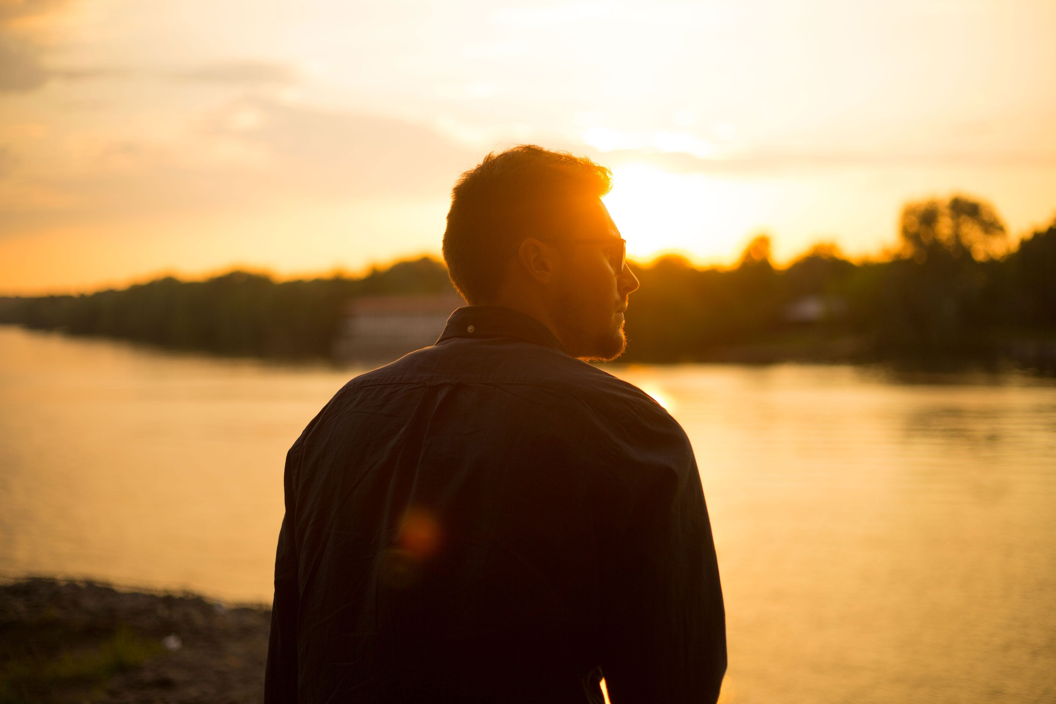 Man Sitting Near Large Body of Water Under Clear Sky during Sunset