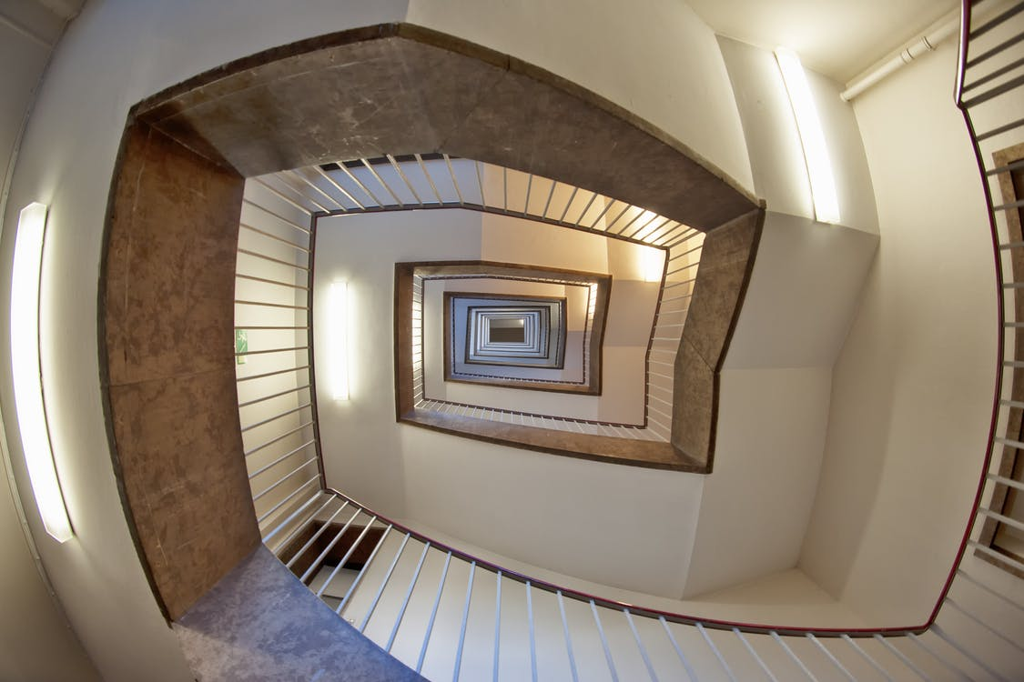 Low Angle Photo of Brown and White Spiral Stairs Building