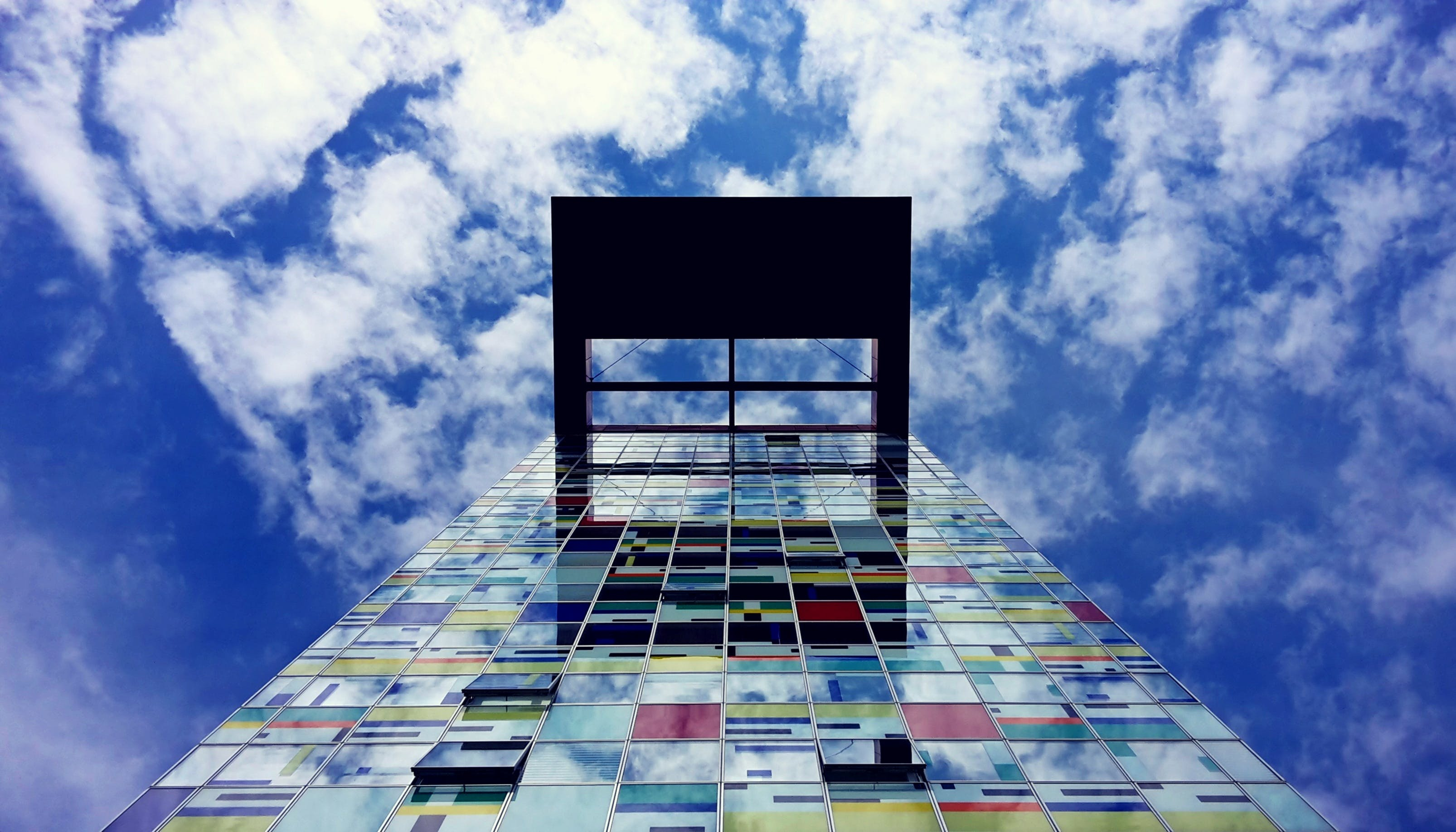 Low Angle Photography of Glass Building Under White Cloud and Blue Sky during Daytime