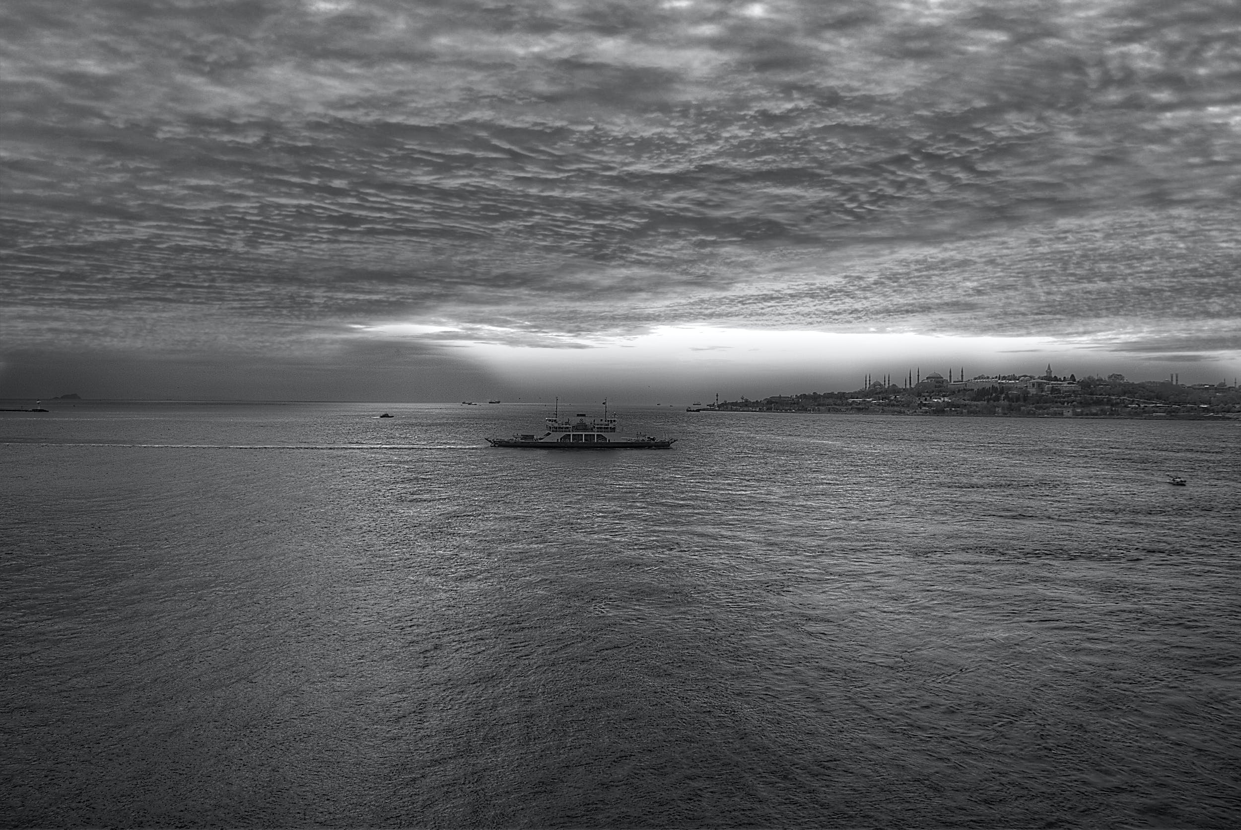Gray Scale Photo of a Boat on Body of Water Under Cloudy Sky