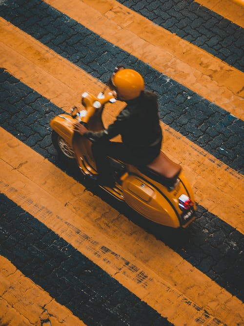 Person Riding on Yellow Motor Scooter on Road