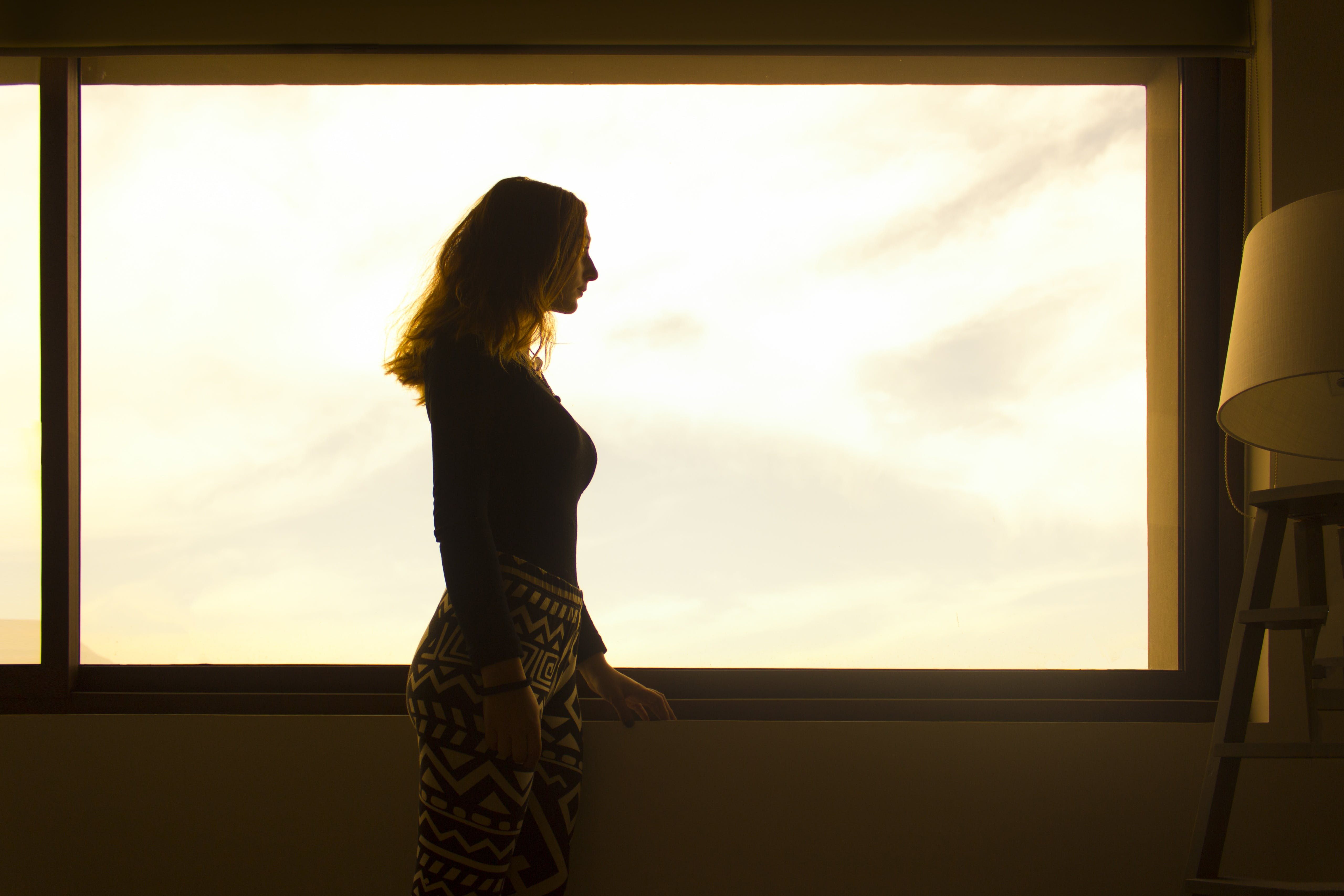 Woman in Black Long Sleeve Shirt and Tribal Leggings Standing by the Window during Daytime
