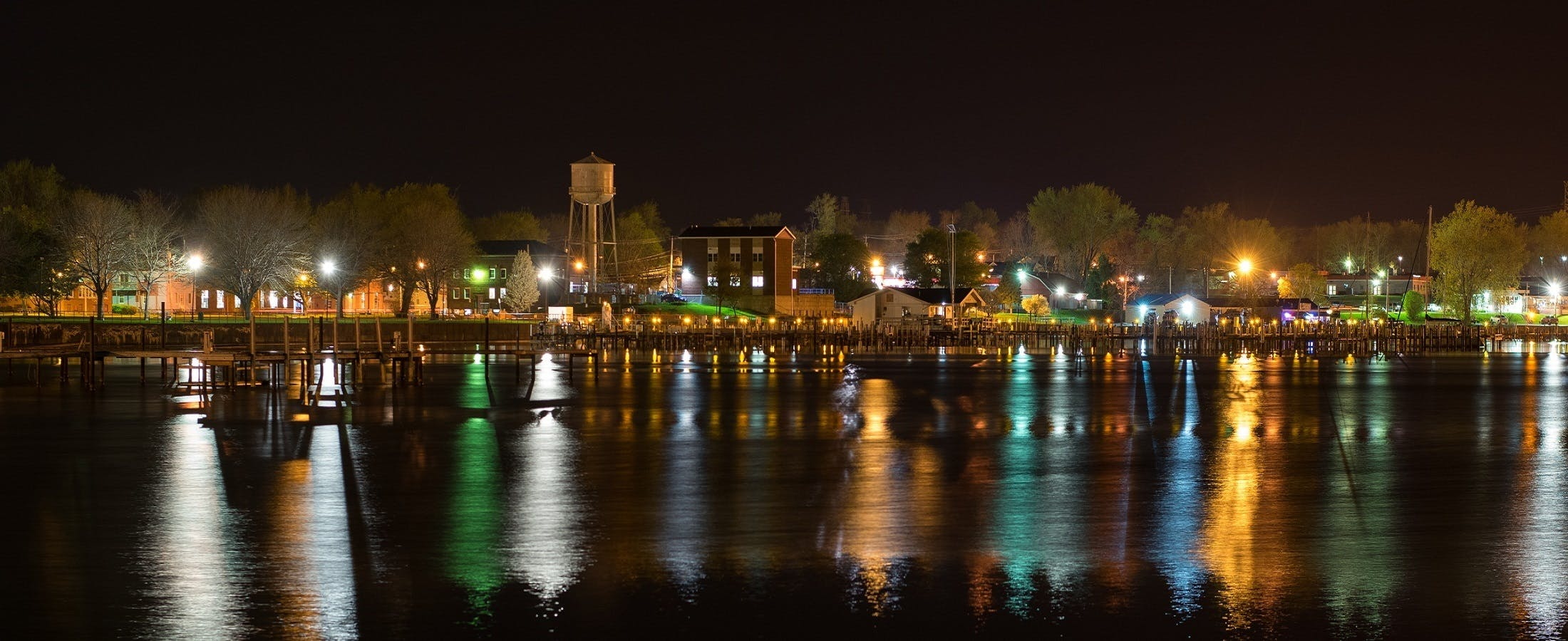 Landscape Photography of Town Near Body of Water during Nightime