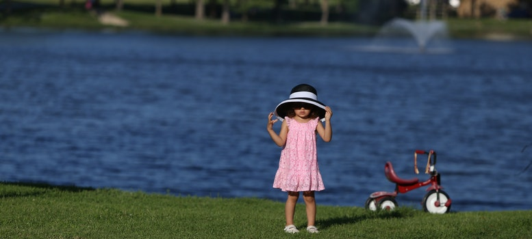 Kid in Pink Dress With White and Black Sun Bucket Hat Beside the Red Pedal Trike in Front of Body of Water