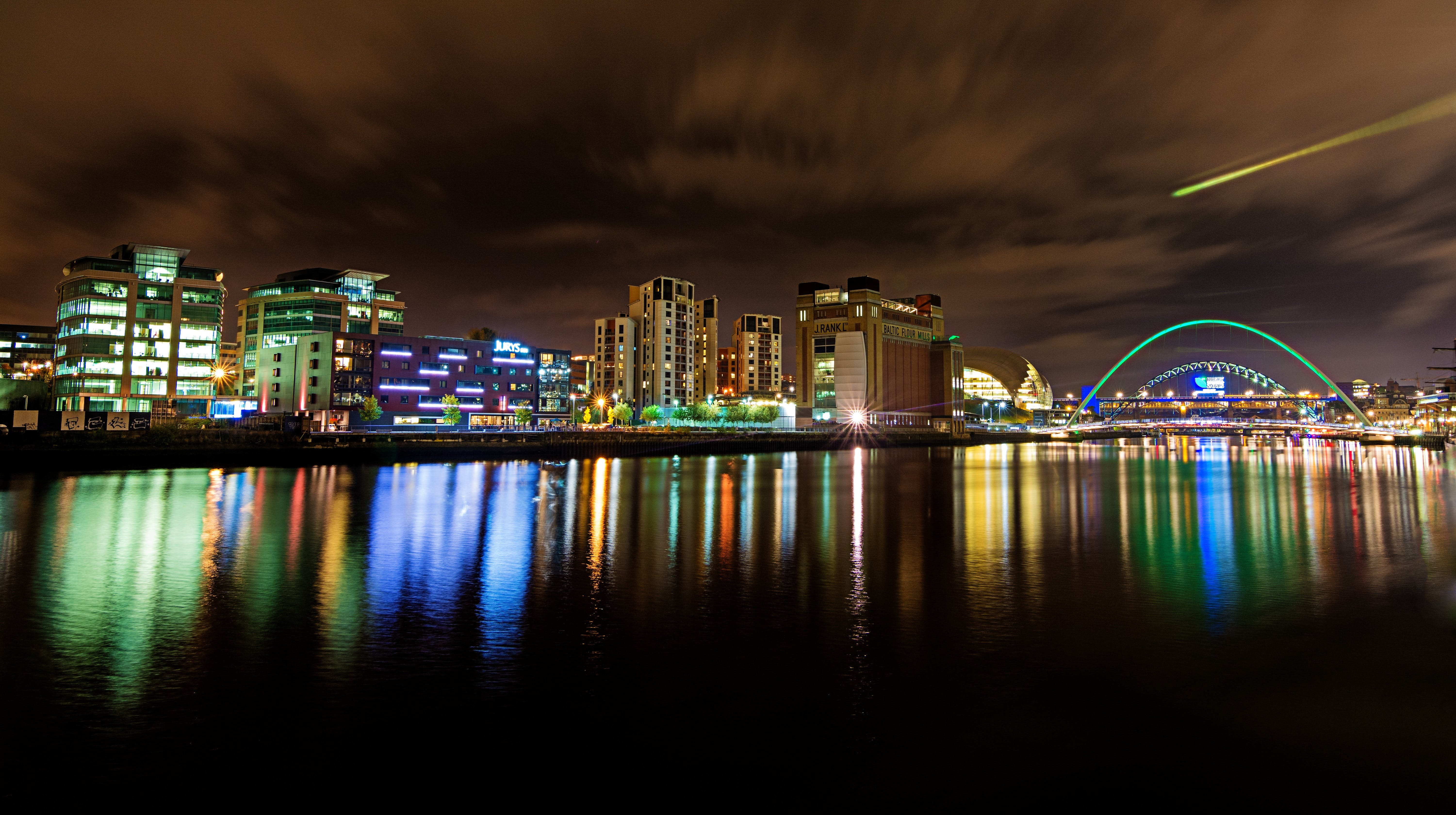 Cityscape at Nighttime Reflecting on Body of Water