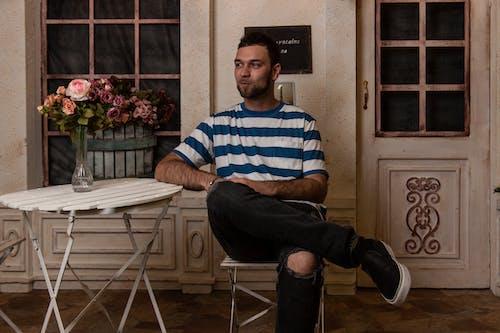 Man Sitting In Chair Facing Sideways