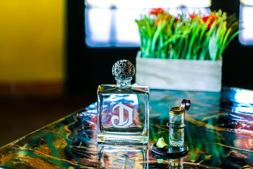 Clear Glass Perfume Bottle on Table