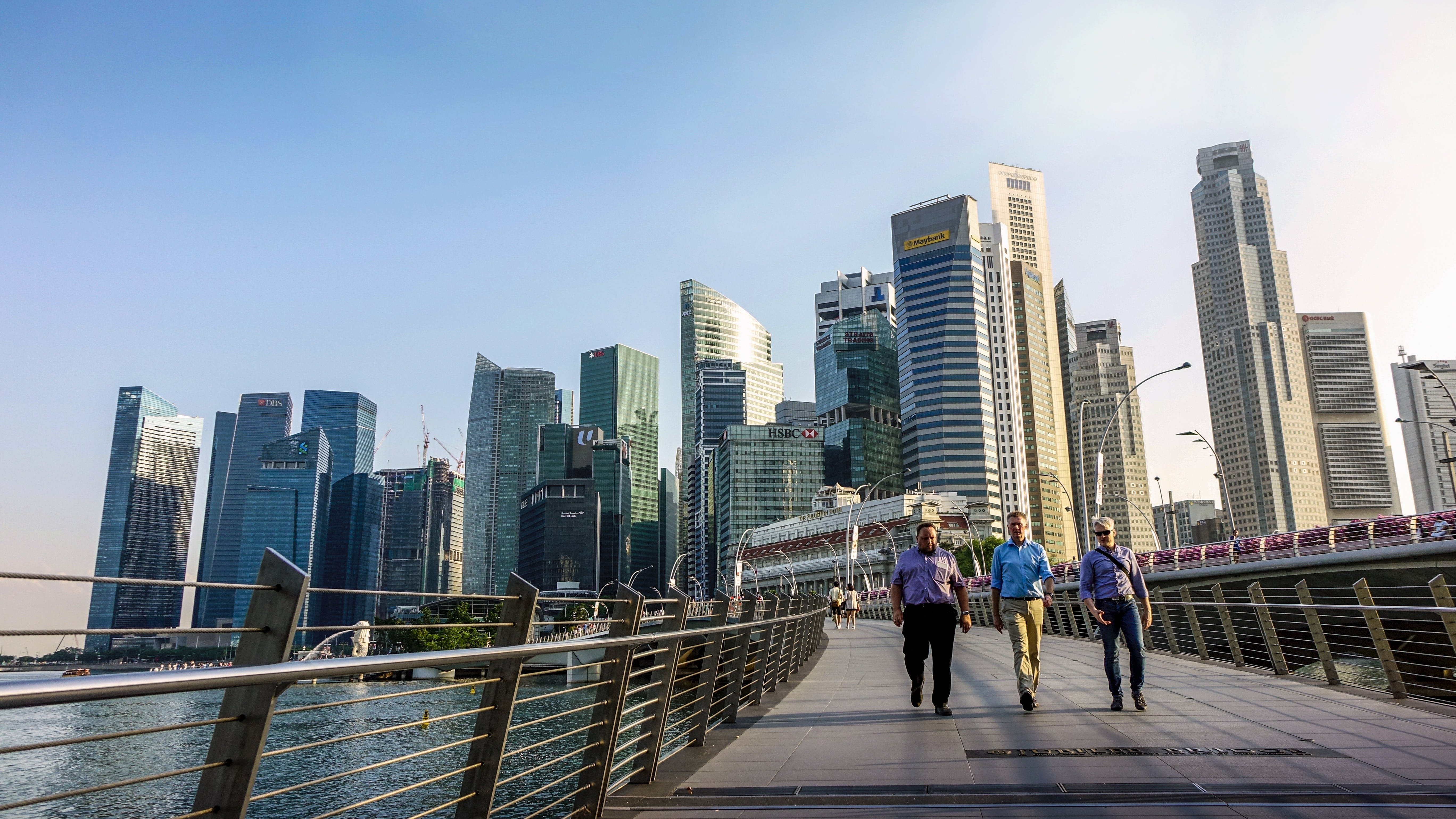Three Men Walking on Bridge in Front of High Rise Buildings at Daytime