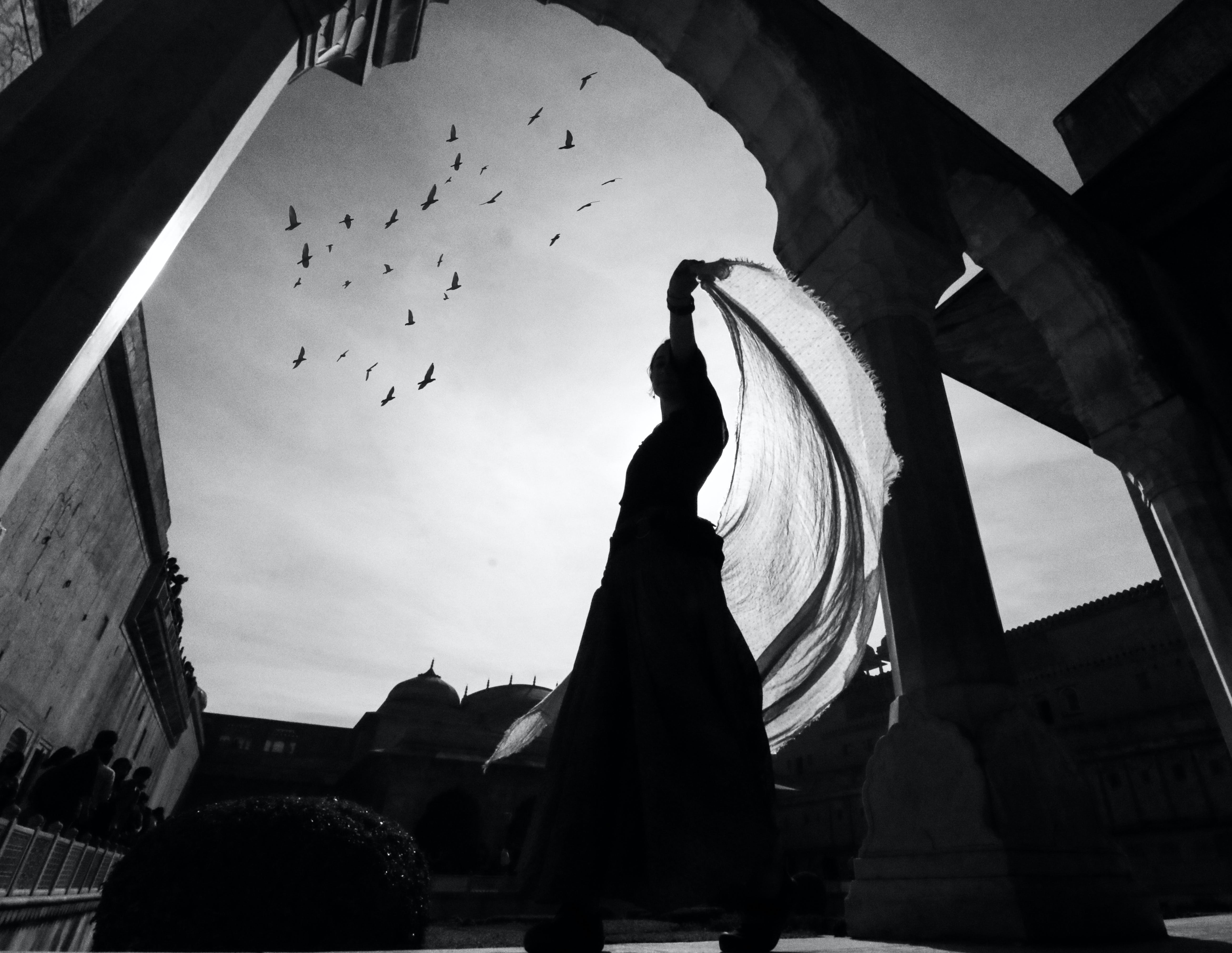 Low Angle View of Silhouette of Woman Standing Near Building