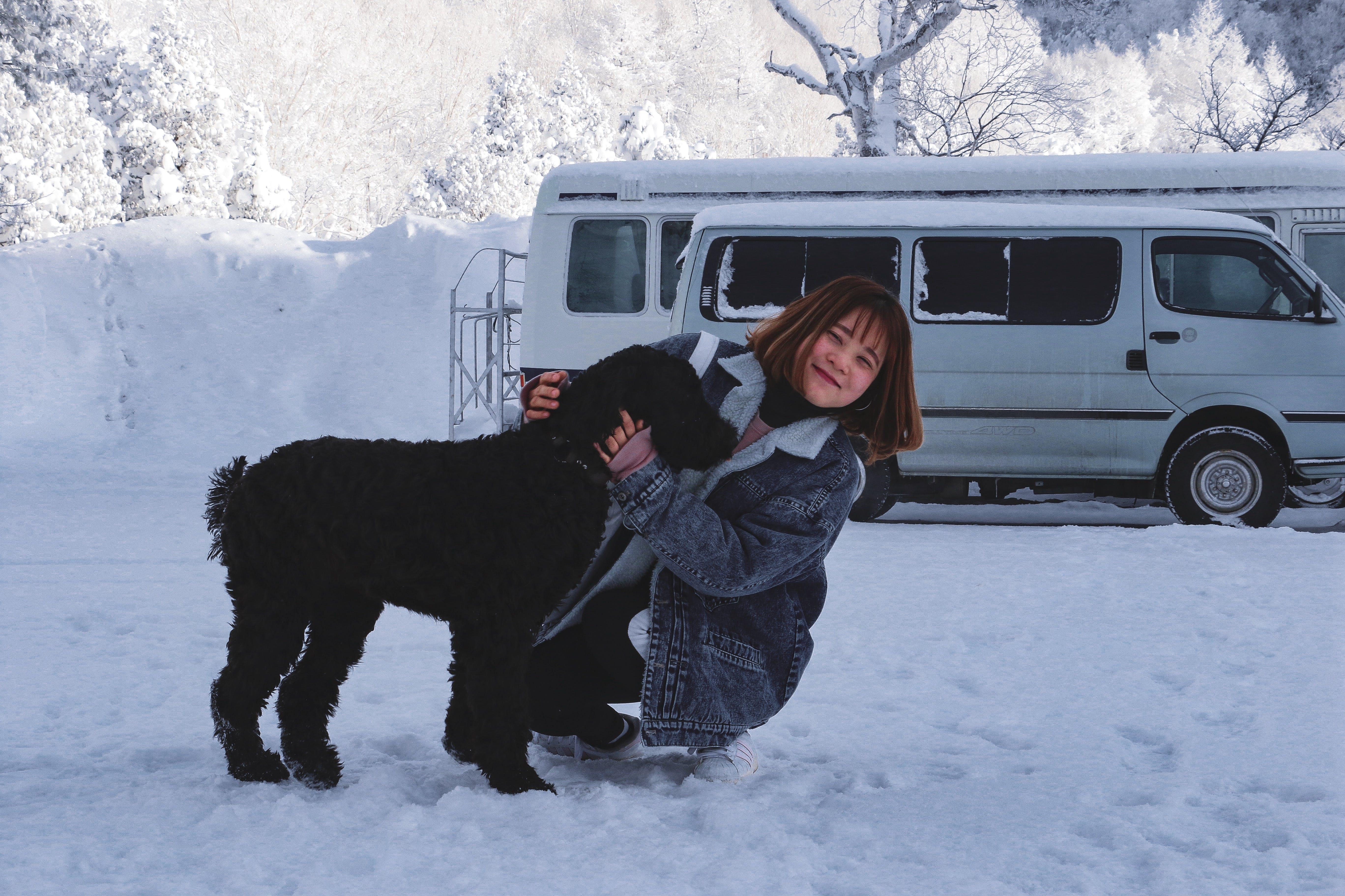 Woman Hugging Short-coated Black Dog