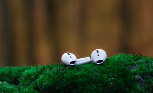 Shallow Focus Photography of White Airpods on Green Surface