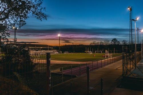 Photos gratuites de aube, barrière, clairière, terrain de sport
