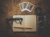 camera, notebook, pencil