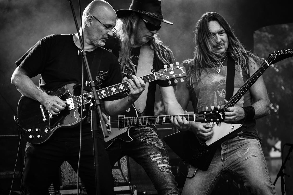 Group of Men Playing Guitar in Concert in Grayscale Photo