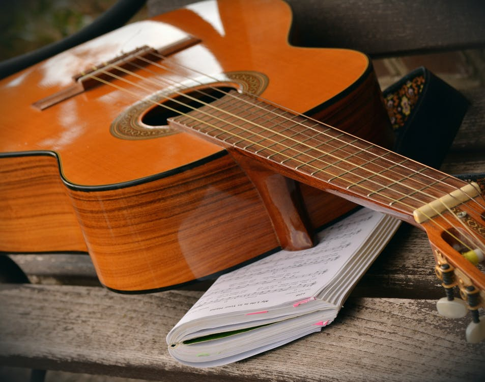 Brown Acoustic Guitar on White Music Note Book