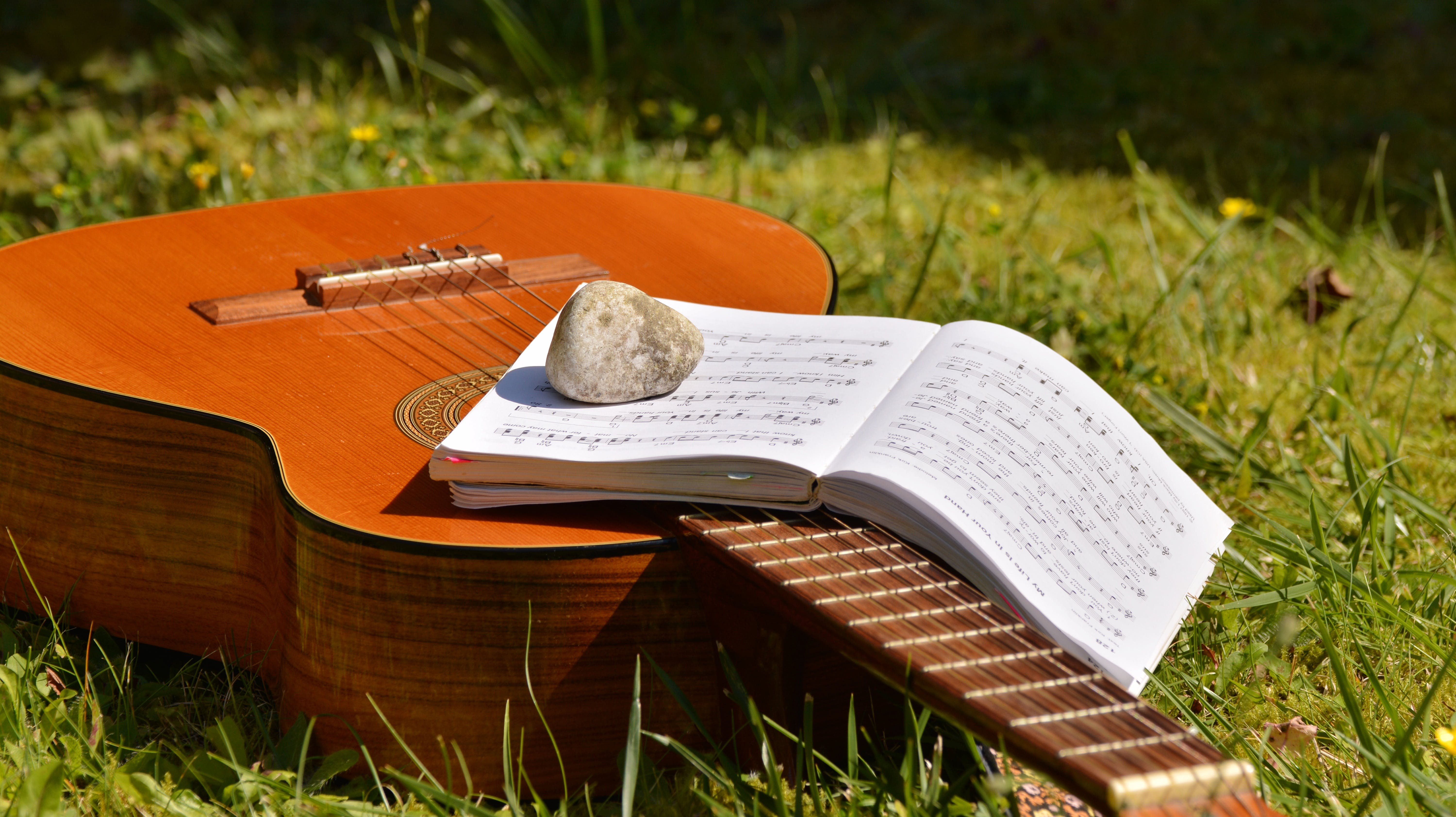 Song Book on Brown Classical Guitar on Green Grass during Daytime