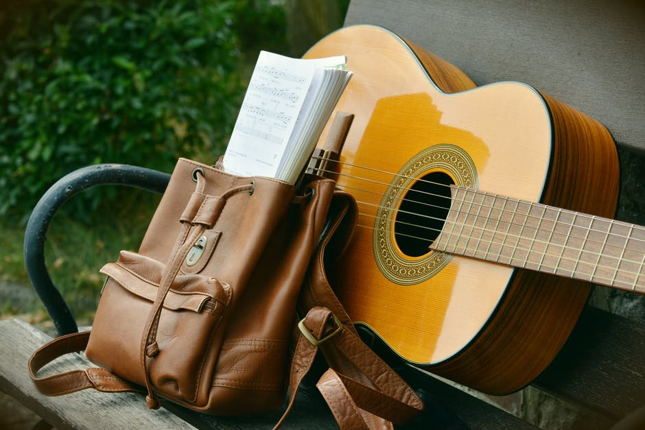 Brown acoustic guitar beside brown leather bucket backpack on brown wooden bench