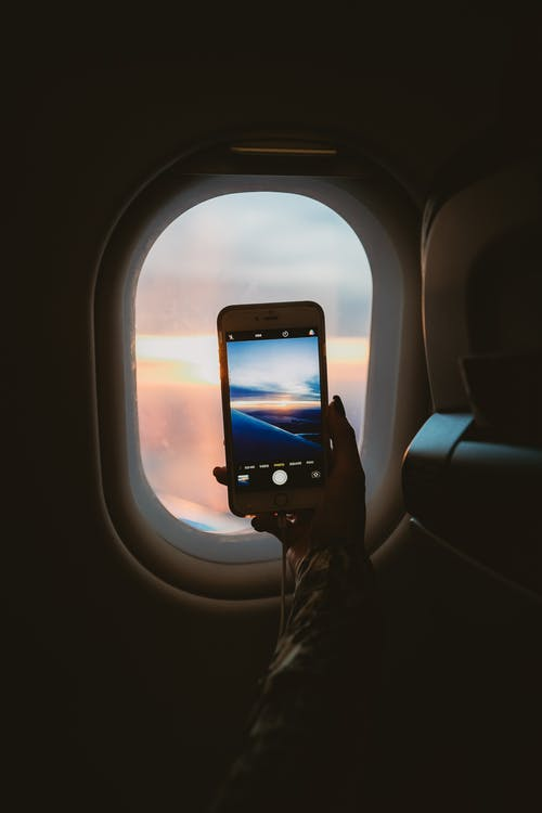 Person Holding Smartphone Inside Airplane