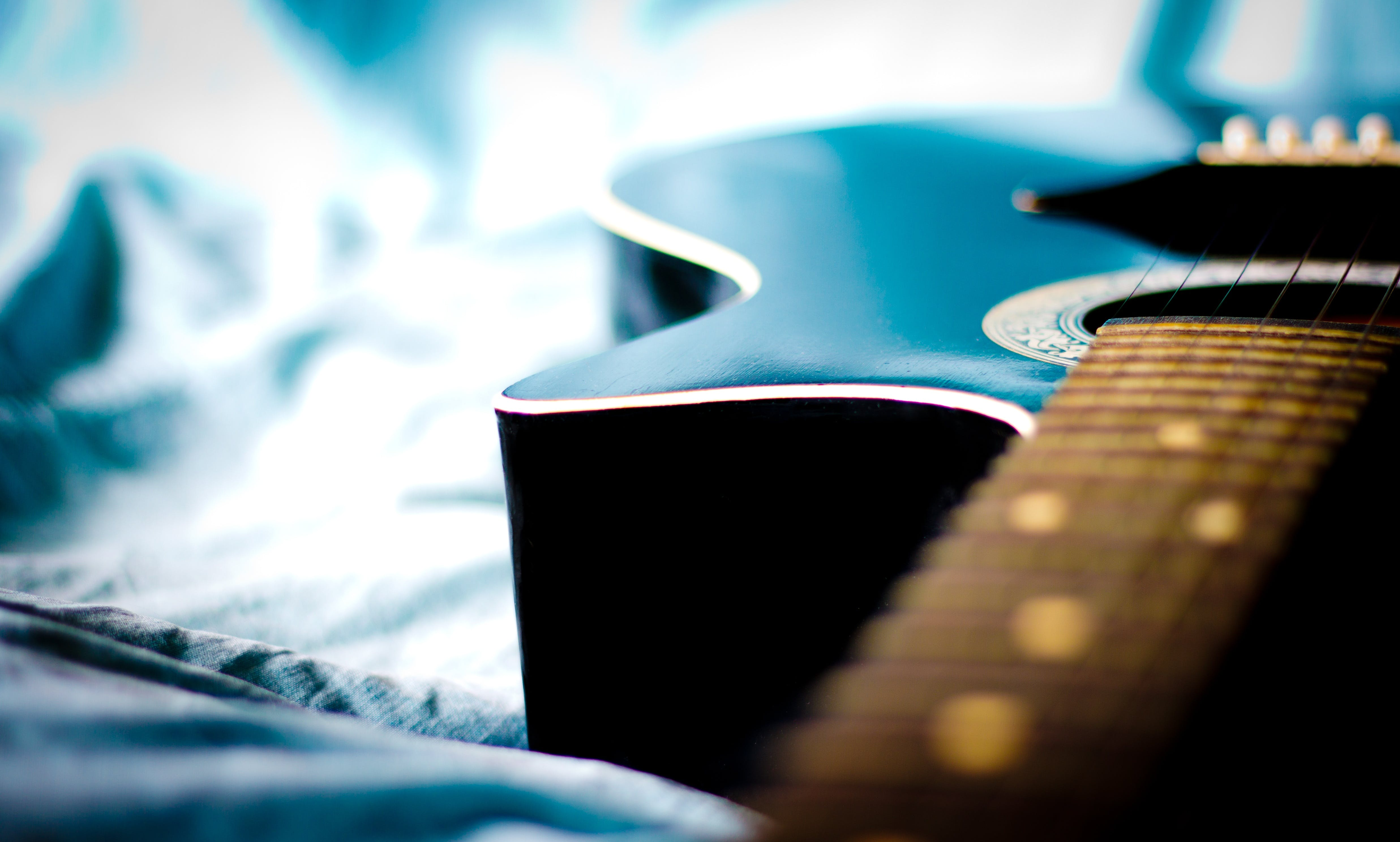Black Acoustic Guitar in Grey Textile Close Up Photo