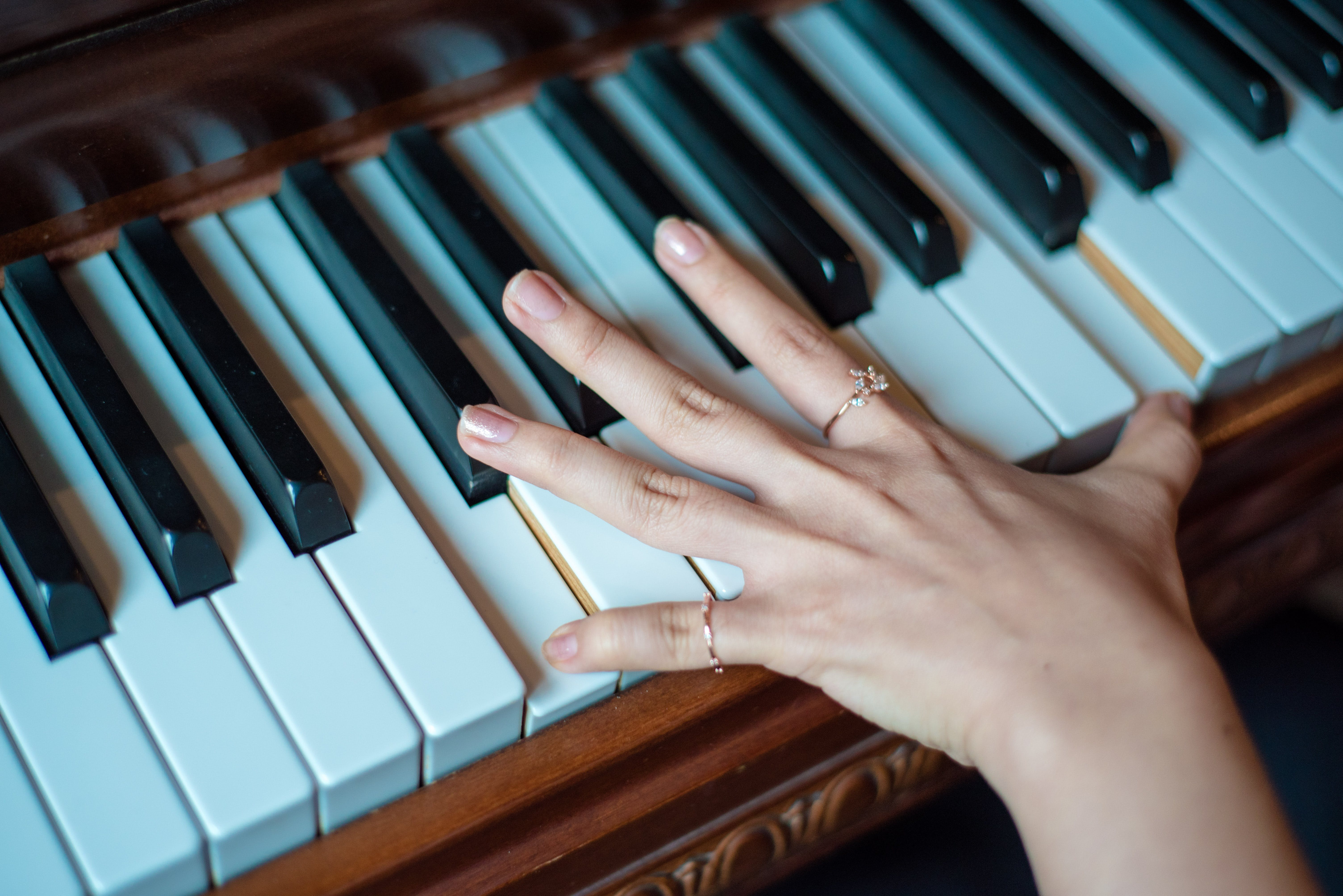 Brown Wooden Piano Used by a Person Using 2 Fingers