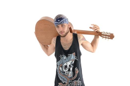 Man in Black and Grey Tank Top Carrying Brown Classical Guitar