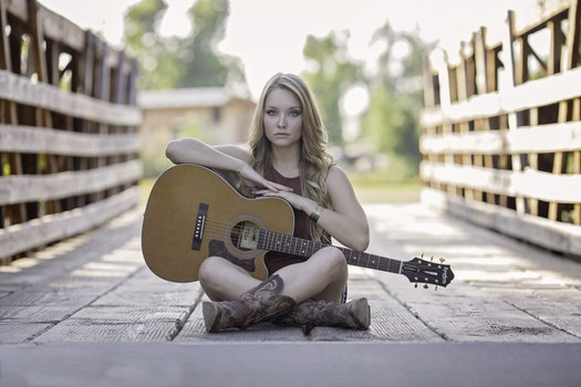 Woman Sitting While Holding Classical Guitar during Daytime