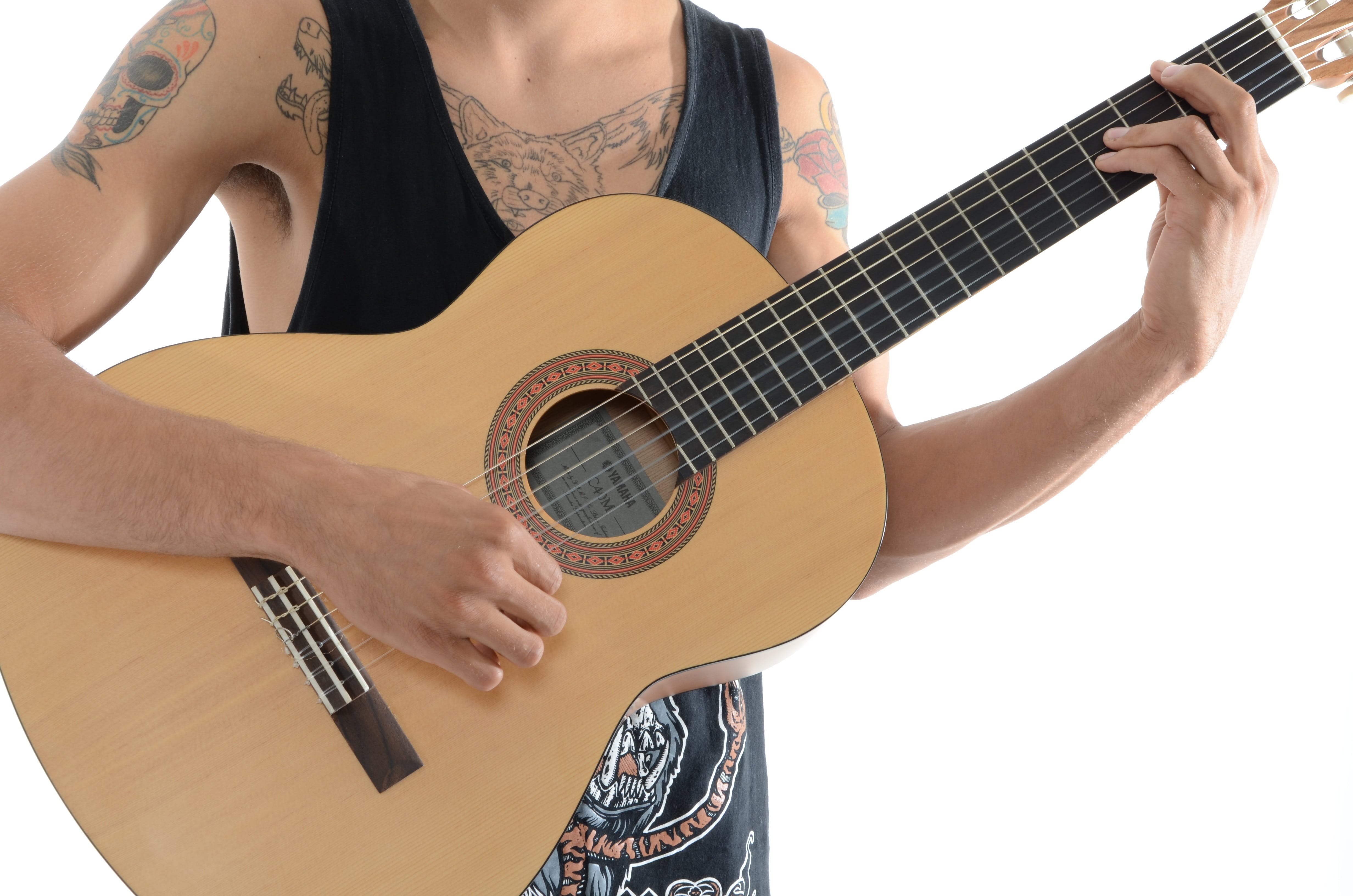 Person Playing a Classic Acoustic Guitar in a White Room