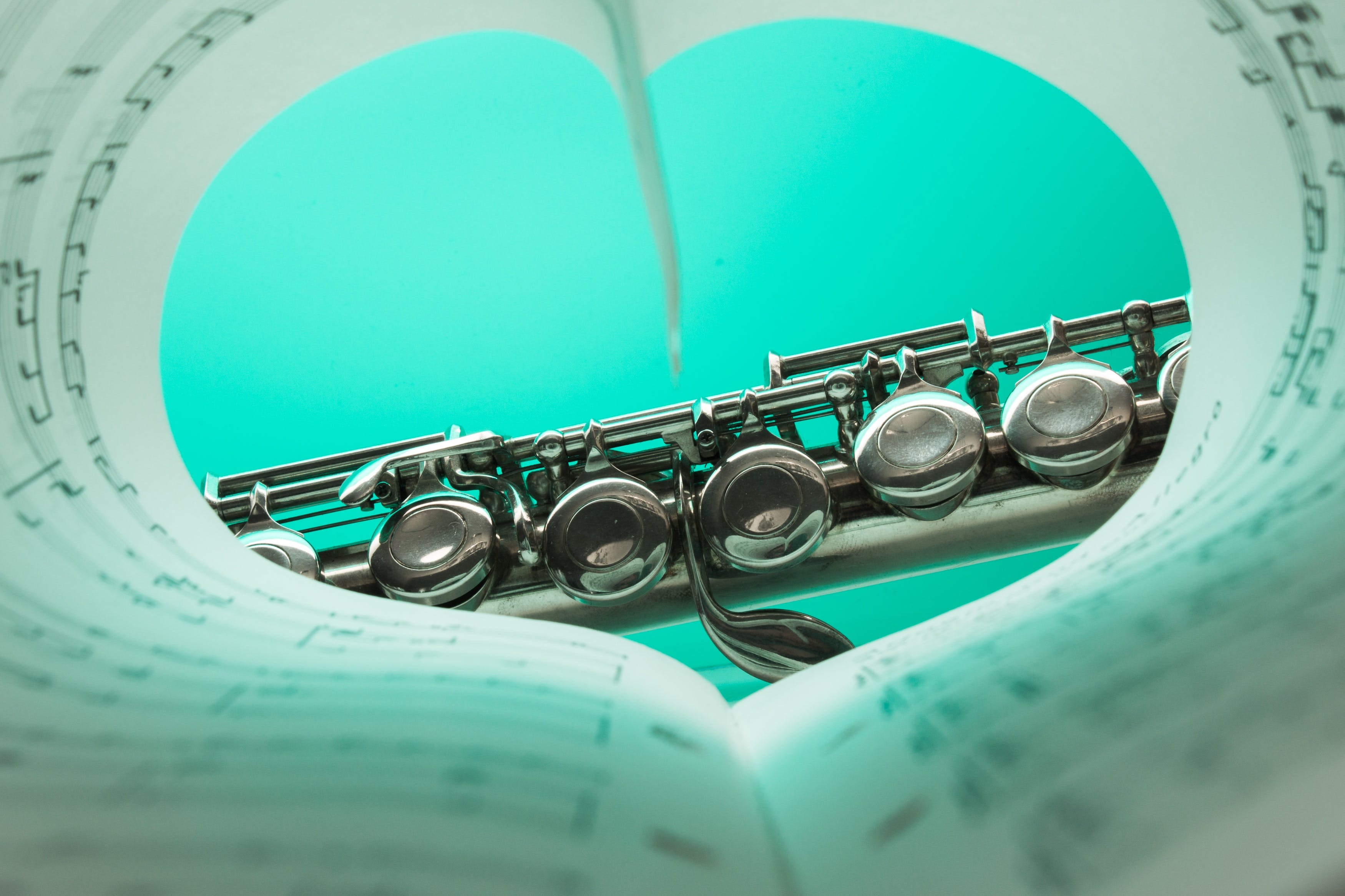 Music Note Book and Silver Soprano Flute Close Up Photography