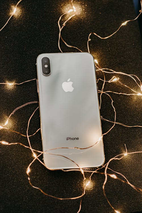 Silver Iphone X Lying on Pre-lit String Lights