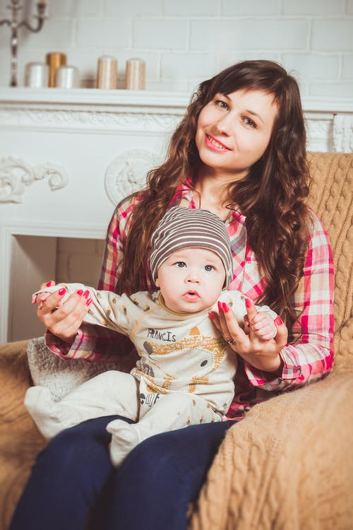 Woman Wearing Red And White Plaid Shirt Sitting On Chair Holding Baby