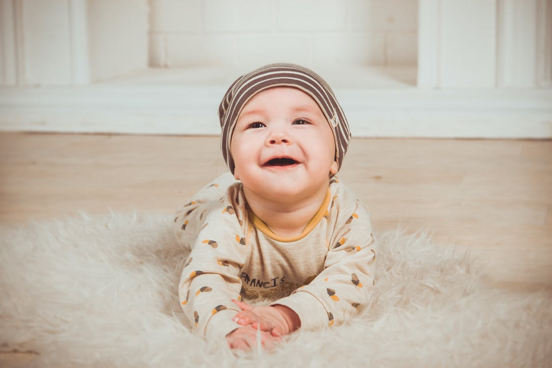 Baby Lying On White Fur Textile