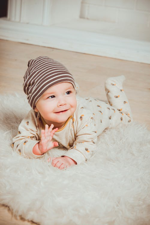 Smiling Baby Lying on White Mat