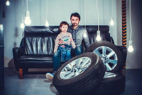 Man With a Boy Sitting on Sofa