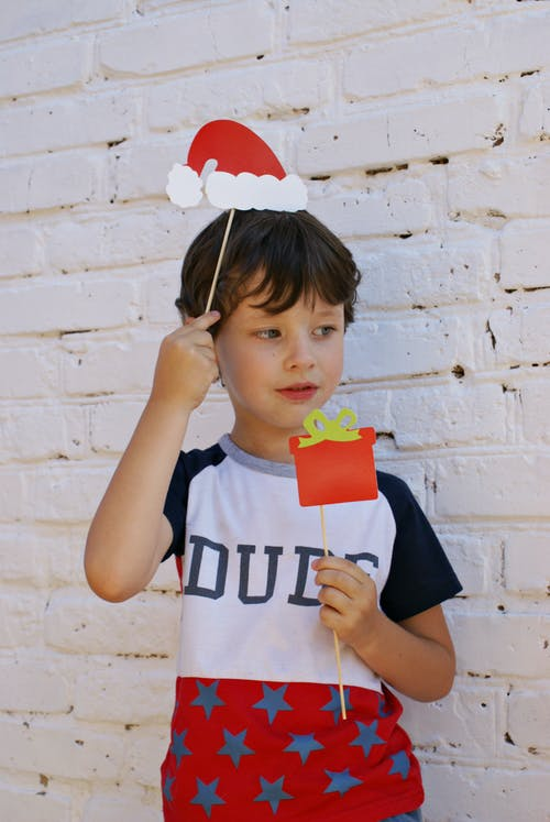 Photo of a Boy Holding Red Christmas Card