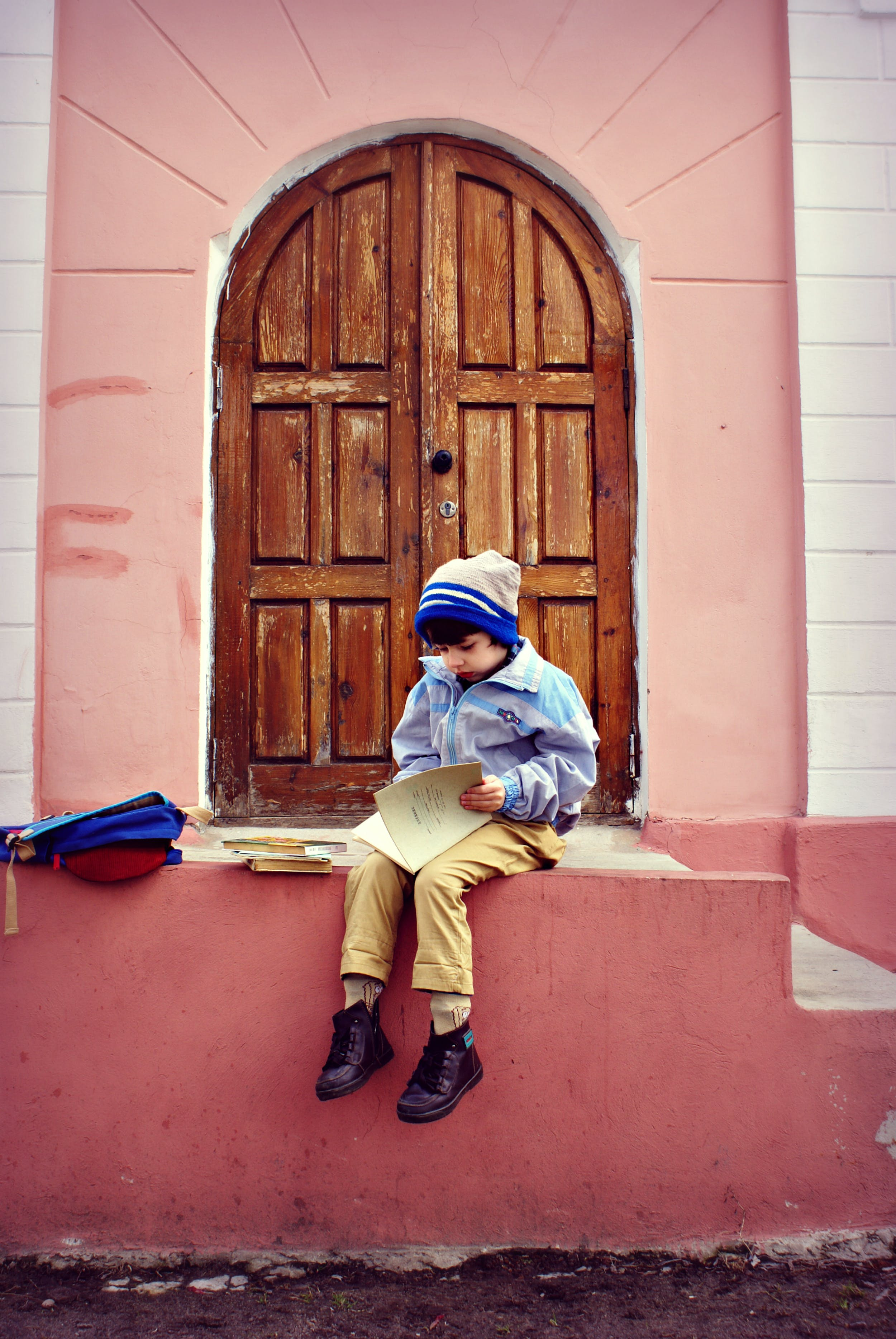 Boy Sitting On Stairs Holding Book