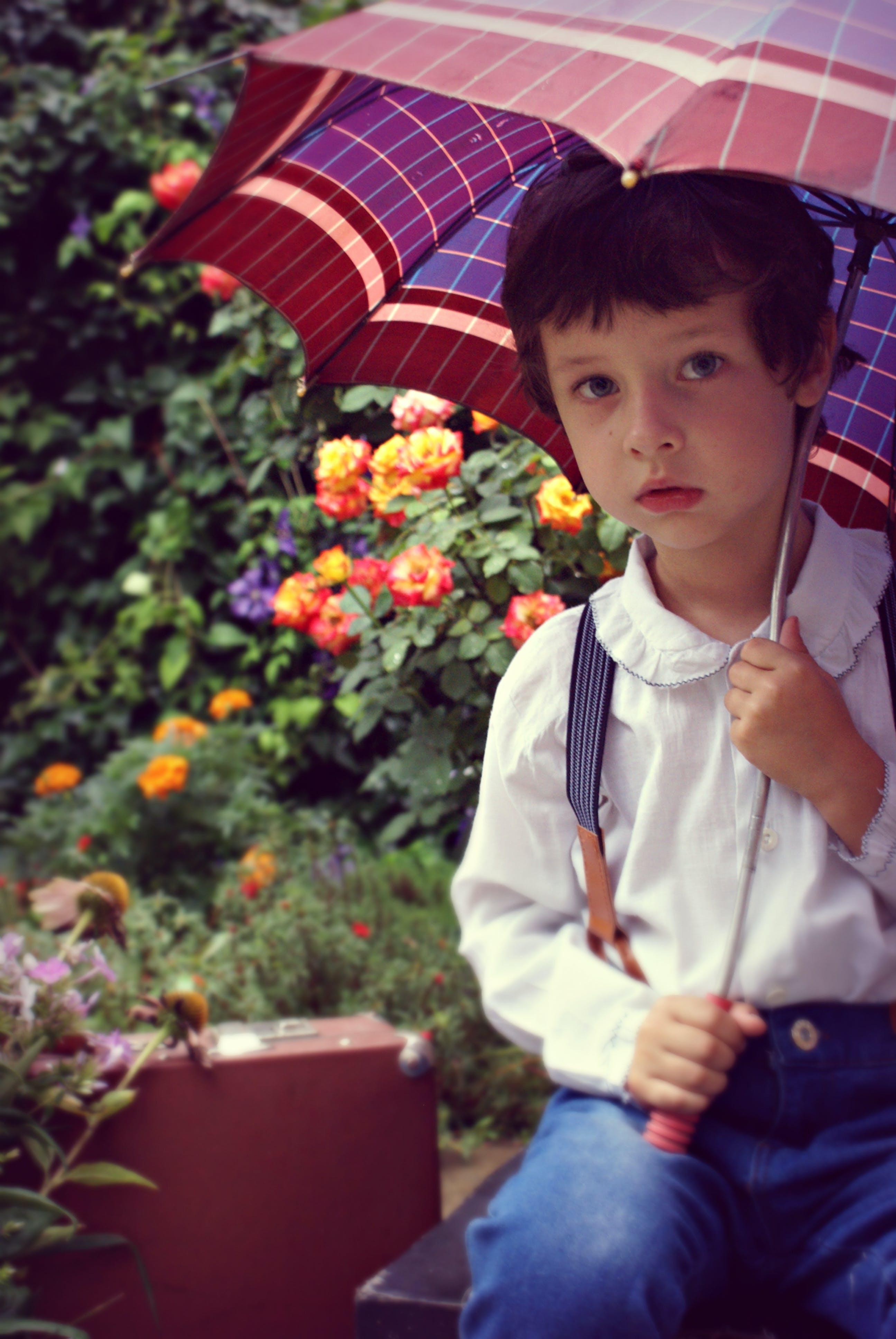 Boy Covering Himself Under Red Umbrella