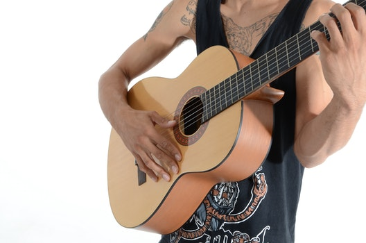 Person in Black Tank Top Playing Acoustic Guitar