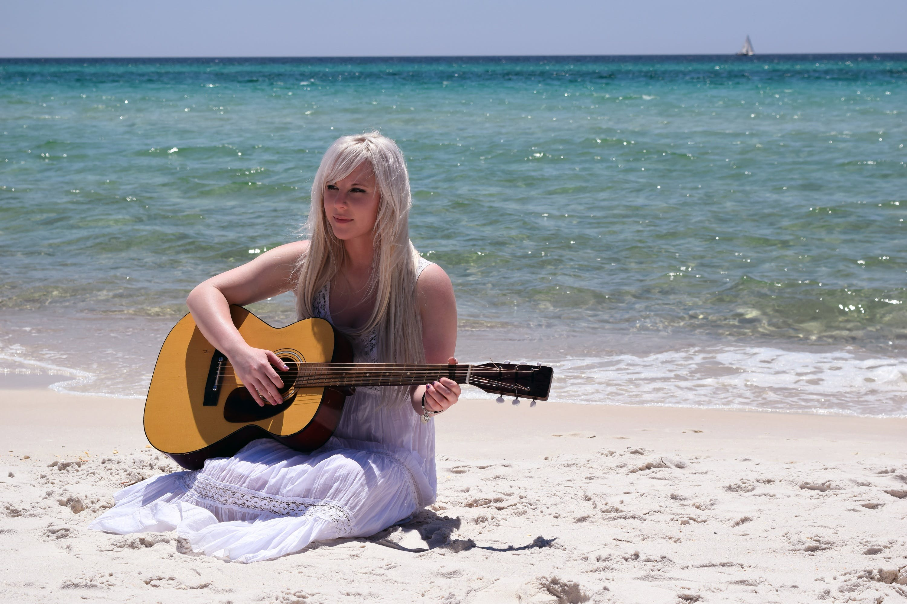 Blond Woman Playing Spruce Top Dreadnought Acoustic Guitar by the Seashore