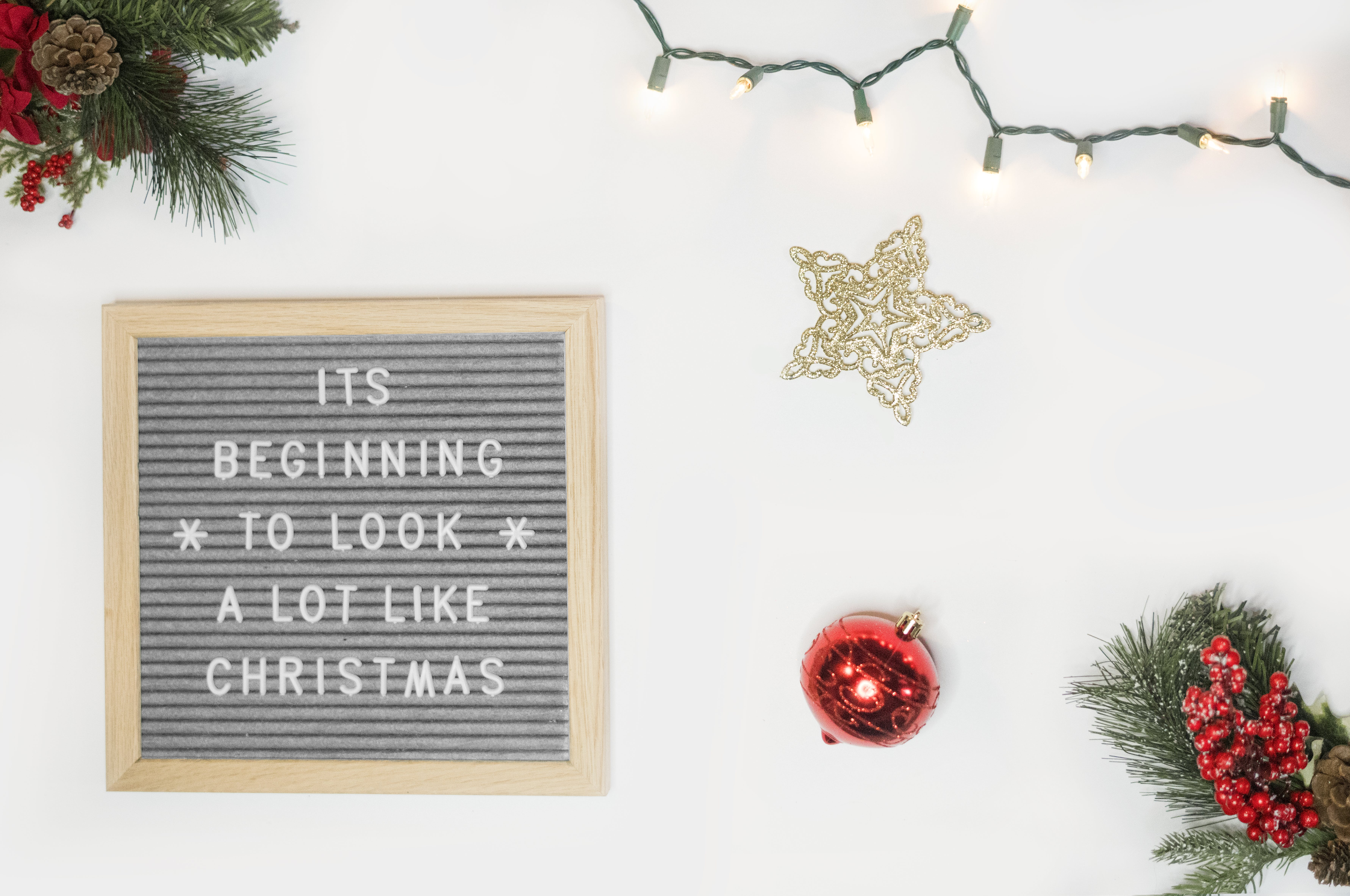 It's Beginning to Look a Lot Like Christmas Board Decor Beside Star and Red Bauble Flatlay Photography