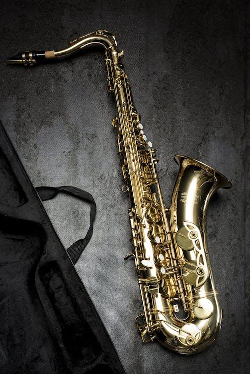 Saxofón De Latón Sobre Mesa Gris Cerca De Bolsa Negra