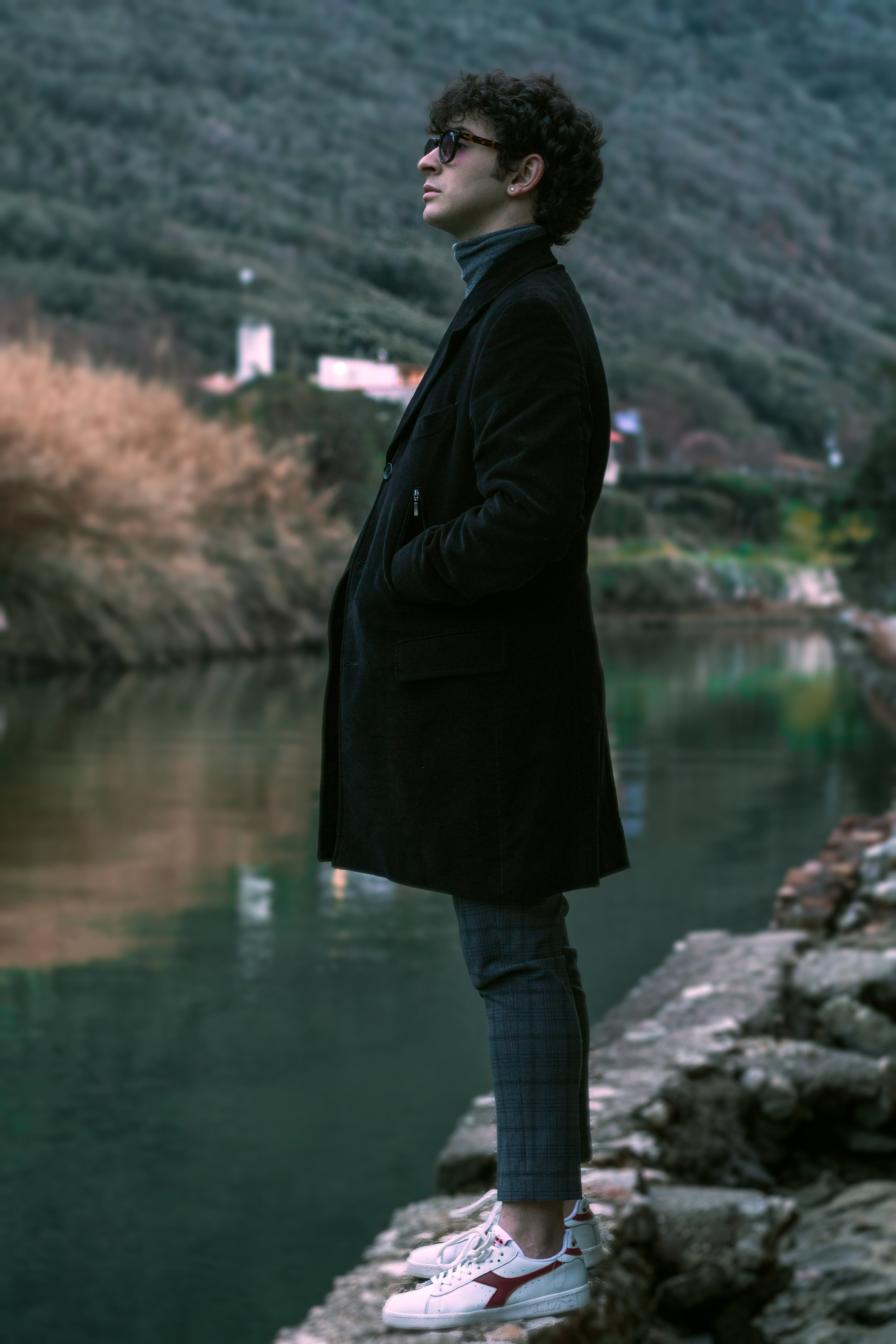 Man Wearing Coat Standing Beside Body of Water