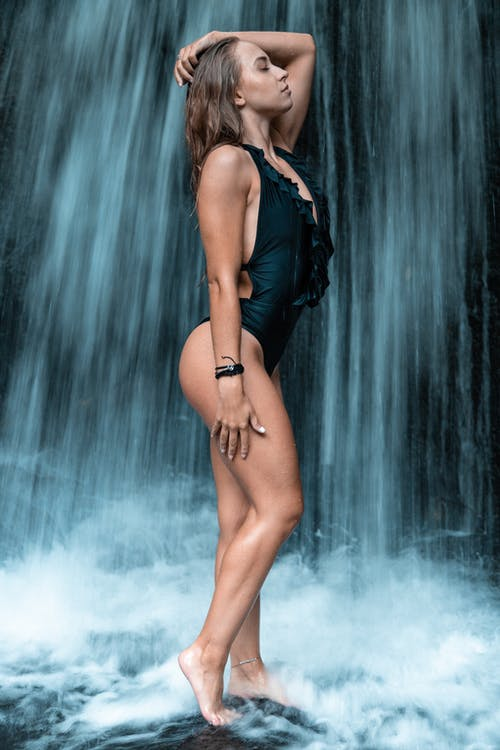 Woman In Black One Piece Standing In Front Of Waterfall