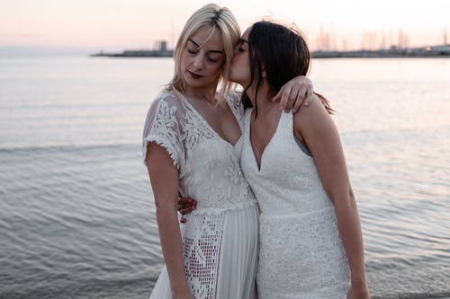 Woman Kissing Woman While Standing Near Body of Water
