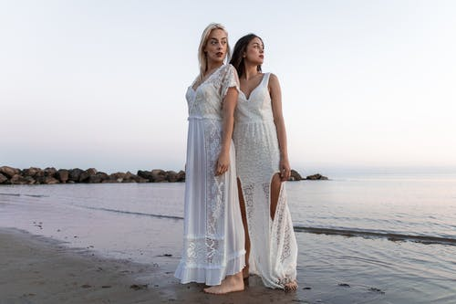 Two Women Wearing White Lace Dress At The Beach